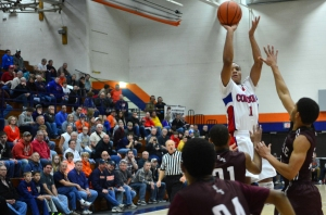Senior leader Devin Gage goes up for the shot over the outstretched arms of the defenders. Photo: (Sun Times)